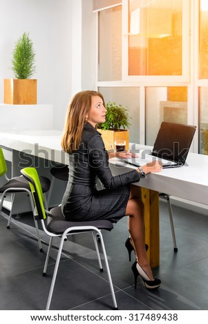 Business, technology and green office concept - young successful businesswoman with laptop computer at office. Woman using tablet computer