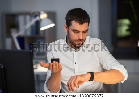 business, technology and internet of things concept - businessman using smart speaker and watch at night office