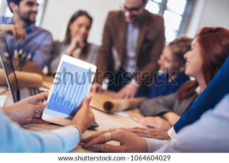 Business, technology and office concept - business team on meeting in modernoffice interior and working on laptop. Digital tablet in the foreground #1064604029