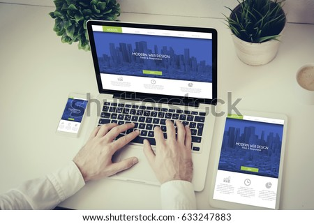 business, technology and responsive design concept: hands writing on a laptop with phone and tablet fresh modern design