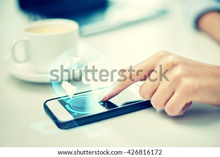 business, technology, communication, leisure and people concept - close up of woman hand with smartphone and globe hologram #426816172