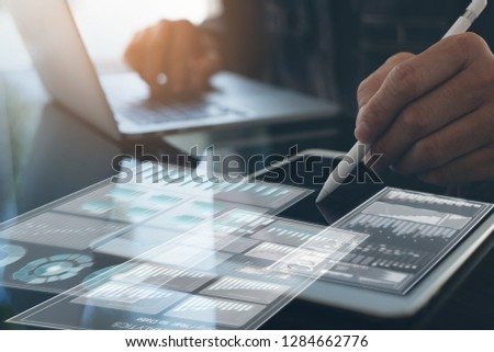 Business technology concept. Business man busy working on laptop computer, digital tablet and electronic pen with marketing report, financial graph and  computer dashboard on screen in modern office. #1284662776