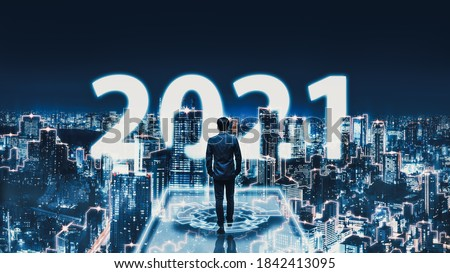 Business technology concept, Professional business man walking on future network Tokyo city background with new year 2021 text and futuristic interface graphic at night in Japan