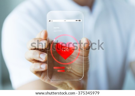 business, technology, health care and people concept - close up of male hand holding and showing transparent smartphone with heart rate icon #375345979