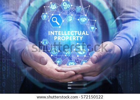 Business, Technology, Internet and network concept. Young businessman shows the word on the virtual display of the future: Intellectual property