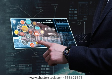 Business, Technology, Internet and network concept. Young businessman working on a tablet of the future, he sees the inscription: asset management