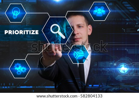 Business, Technology, Internet and network concept. Young businessman working on a virtual blackboard of the future, he sees the inscription: prioritize