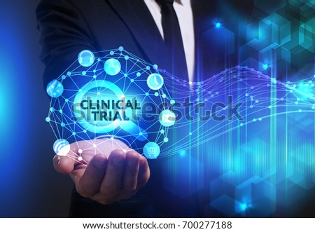 Business, Technology, Internet and network concept. Young businessman working on a virtual screen of the future and sees the inscription: Clinical trial #700277188