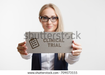 Business, Technology, Internet and network concept. Young girl holding a sign with an inscription clinical trial #709073155