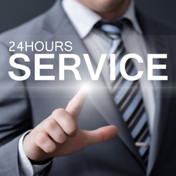 business, technology, internet and networking concept - businessman pressing 24 hours service button on virtual screens