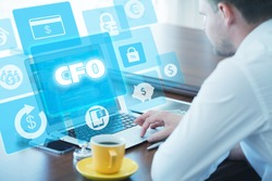 Business, technology, internet and networking concept. Young businessman working on his laptop in the office, select the icon CFO â?? Chief Financial Officer on the virtual display.