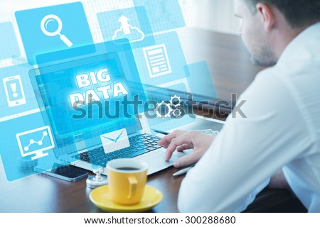 Business, technology, internet and networking concept. Young businessman working on his laptop in the office, select the icon big data on the virtual display. #300288680
