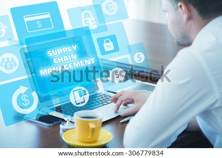 Business, technology, internet and networking concept. Young businessman working on his laptop in the office, select the icon supply chain management  on the virtual display.
