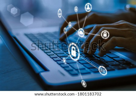 Business, technology, internet and networking concept. Young businesswoman working on his laptop in the office, select the icon security on the virtual display.Blue tone concept