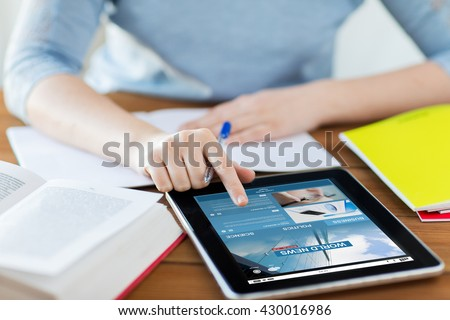business, technology, people, mass media and internet concept - close up of student woman with news web page on tablet pc computer screen and notebook at home