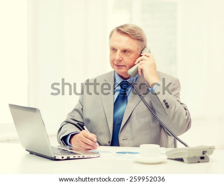 business, technologym communication and office concept - busy older businessman with laptop, charts, coffee and telephone in office