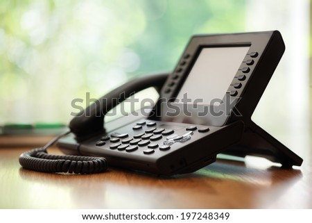 Business telephone with liquid crystal display on a desk in an office #197248349