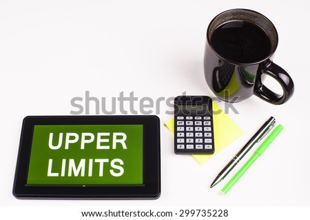 Business Term / Business Phrase on Tablet PC - Cup of coffee, Pens, Calculator and a green/yellow note pad on a White surface - White Word(s) on a green background - Upper Limits