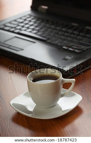 Business theme with laptop and coffee - stock photo