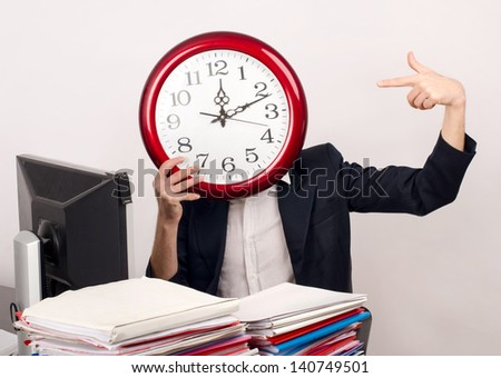 Business time. Business man in the office holding and pointing to a big clock covering his face.