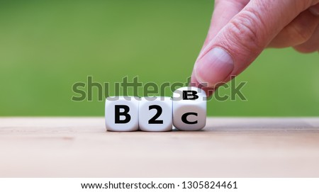 """Business to Business or Busness to Consumer? Hand turns a dice and changes the expression """"B2B"""" to """"B2C"""" (or vice versa)"""