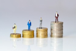 Business toy people standing on stack of Euro coins. figurine symbol for increasing or reduction expenses for salarys. miniature businessman on increasing high stack of coins on bright background.