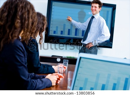 Business training at office, happy businessman presenting successful financial numbers on screen of plasma TV at meeting room, smiling.