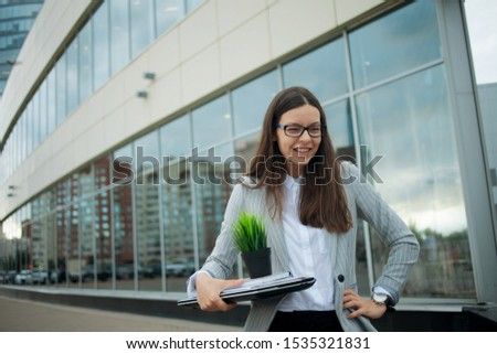 Business transfer, transition to a better job. Voluntary dismissal, a young woman resigned from the company. Happy Girl on the background of the business center Сток-фото ©