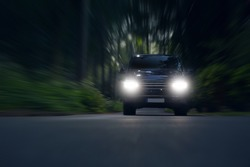 Business transfer vip van ride fast in forest. Luxury minivan car in motion. Car go fast with bright lights