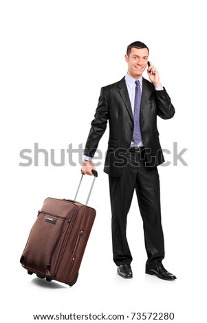 Business traveler carrying a suitcase and talking on a cell phone isolated on white background