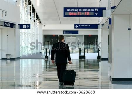 Business traveler walking thru airport terminal