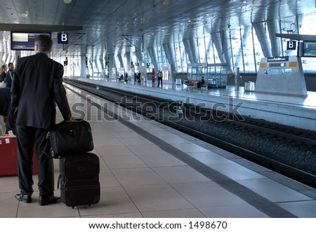 Business Trip. A businessman is waiting for the train on a modern trainstation.