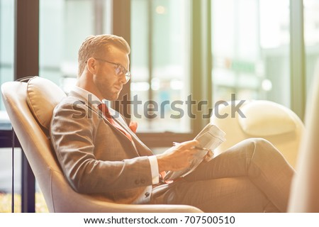 Business trip. Confident professional businessman sitting in the departure lounge and reading a newspaper while waiting for his flight