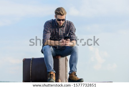 Business trip. Handsome guy traveler. Guy outdoors with vintage suitcase. Luggage concept. Calling taxi. Travel agency. Travel with luggage. Travel blogger. Man sit on suitcase before journey.
