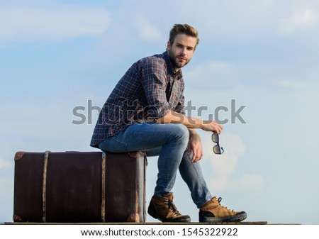 Business trip. Handsome guy traveler. Guy outdoors with vintage suitcase. Luggage concept. Travel with luggage. Travel blogger. Vacation time. Travel agency. Man sit on suitcase before journey.