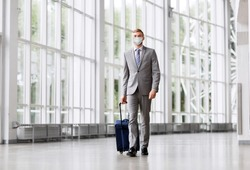 business trip, health and people concept - young businessman walking with travel bag along office building or airport wearing face protective medical mask for protection from virus disease
