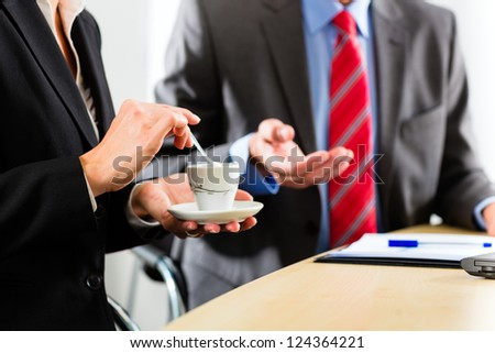 Business - Two businesspeople or professionals have a conversation in an office and drinking coffee or espresso