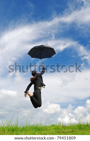 Business umbrella woman jumping to blue sky in grassland with black umbrella