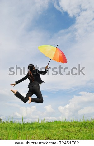 Business umbrella woman jumping to blue sky in grassland with rainbow umbrella