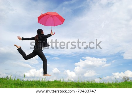 Business umbrella woman jumping to blue sky in grassland with red umbrella