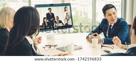 Business video conference meeting in office. People communicate with team using video call in meeting room. Smart tele video meeting connects staff from remote office.