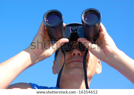 Business vision - man with the binoculars over blue sky