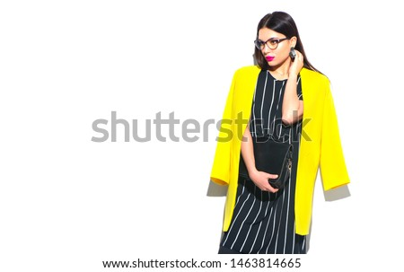 Business wear look style, Beauty sexy fashion model girl in trendy yellow blazer wearing glasses, holding clutch, isolated on white background. Beautiful young brunette woman with trendy accessories