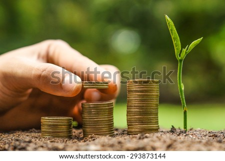 Business with csr practice / hand giving coins to stacks of coins in graph shape with a young plant