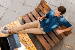 Business without hurrying. Top view of smiling young man holding digital tablet while relaxing outdoors