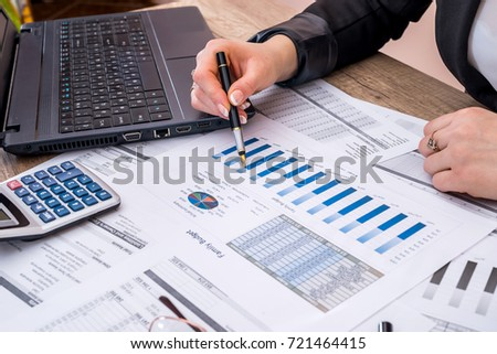 Business woman account annual budget with laptop, pen and graph.