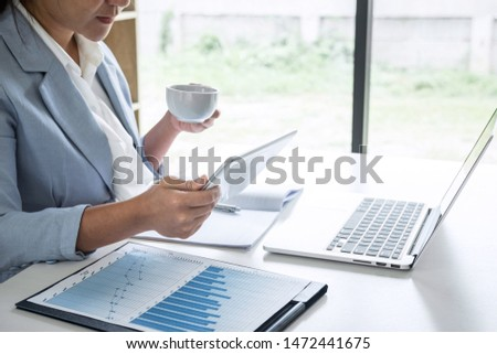 Business woman accountant financier working audit and calculating expense financial annual report balance sheet statement, doing finance checking document and making notes on report paper. #1472441675