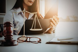 Business woman and lawyers discussing contract papers with brass scale on wooden desk in office. Law, legal services, advice, Justice and real estate concept.