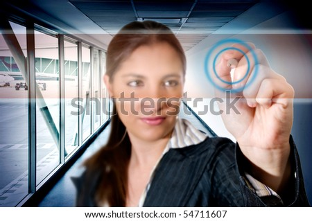 Business woman at airport touching digital screen