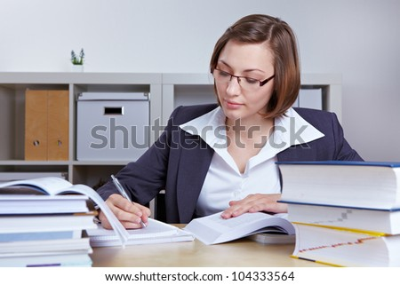 Business woman at her desk in the office doing research with books